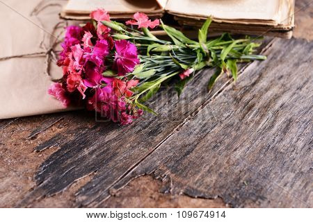 Old book with beautiful flowers and envelopes on wooden table close up