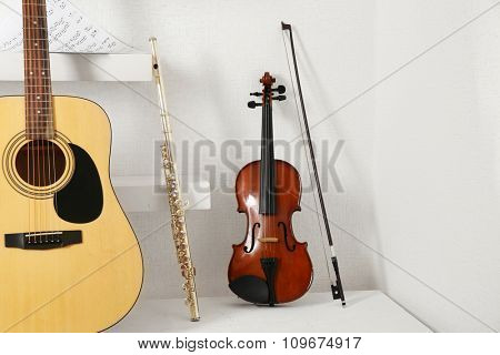 Musical instruments on decorated shelves against white wall background