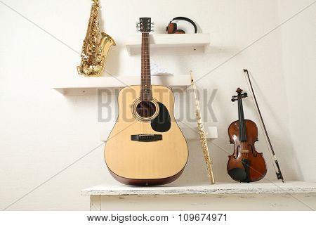 Musical instruments and headphones on decorated shelves against white wall background