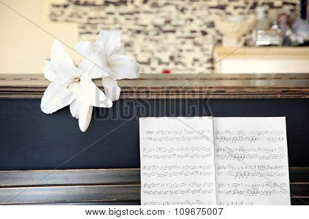 Vintage old classic piano with flower and musical notes, close up
