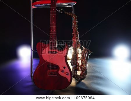 Beautiful golden saxophone and guitar near bar stool on a scene