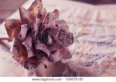 Beautiful paper-made rose on musical notes page background