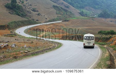 SON LA, VIETNAM - APR 10, 2014: A passenger car running on a S-shape road through Moc Chau highland toward the far north west of Vietnam. Moc Chau is known as a hometown of milk in the country.