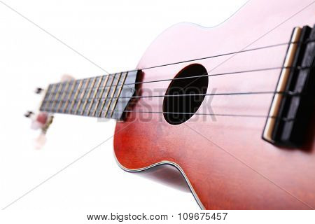 Close-up part of the Hawaiian acoustic guitar isolated on white