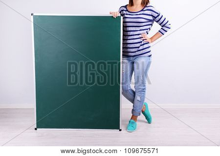 Woman in causal with green blackboard on grey background, close up