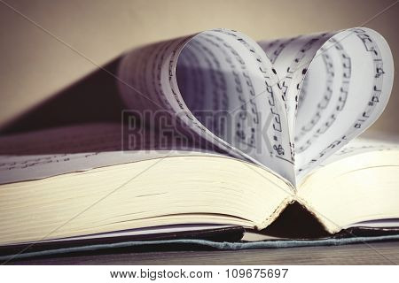 Book pages curved into heart shape on gray background