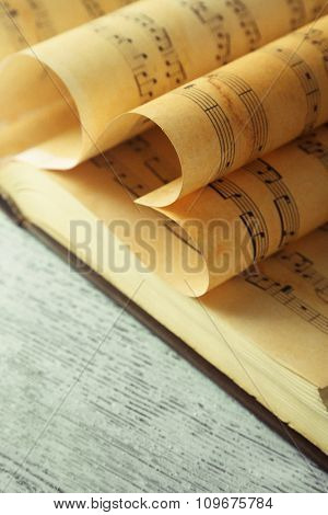 Book pages curved into hearts shapes on table close up