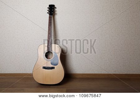 Acoustic guitar propped on wall in the room