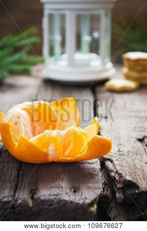 Peeled tangerine, ginger biscuits and white lights on a Christma