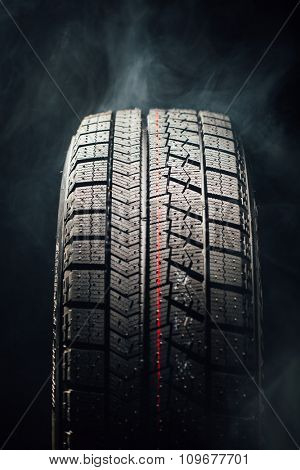 winter tire in smoke, closeup view