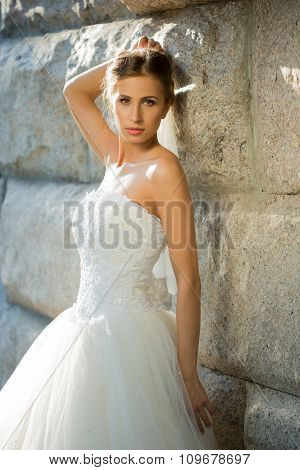 portrait of beautiful bride in the park. backdrop stone wall
