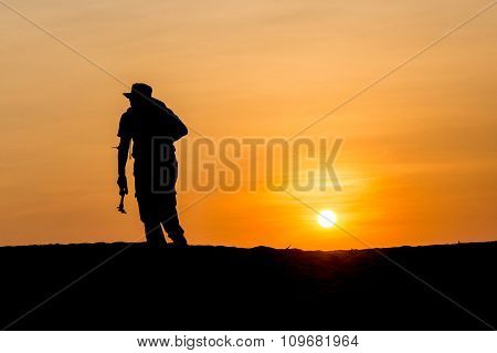 Man In Silhouette Holding A Tripod Walking At Tropical Beach