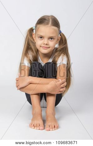 Girl Gymnast Sitting On The Floor Hugging His Legs