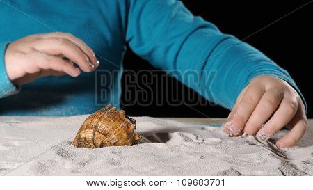 Child playing with sand and shells