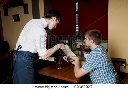Man Makes An Order  To The Waiter At A Restaurant.