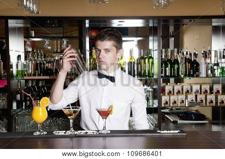 barman standing in front of the bar and making cocktail drinks