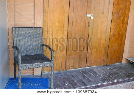 Black Wicker Chair Beside The Wooden Wall