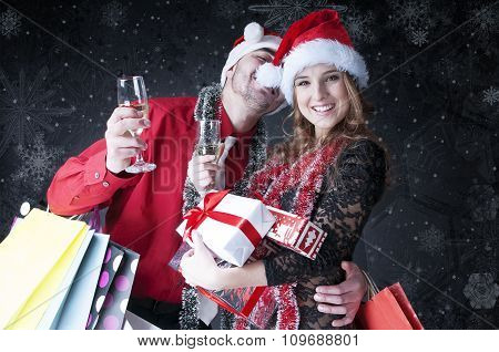 Funny Christmas Couple With Glasses Of Champagne  Covering Snowy Background