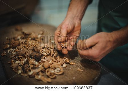 Man cracking walnut  with hands