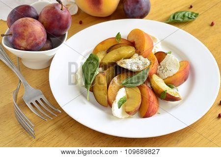 Salad with peaches, goat cheese, plum and basil