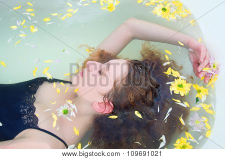Young Woman With Curly Hair Taking A Bath With Herbs