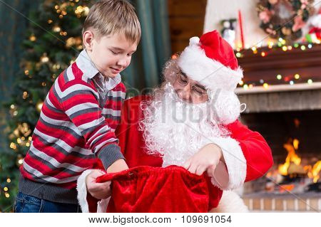 Santa Claus giving a present from sack to child boy near the fireplace and Christmas tree at home.