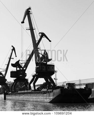 Dark Silhouettes Of Industrial Port Cranes, Danube River