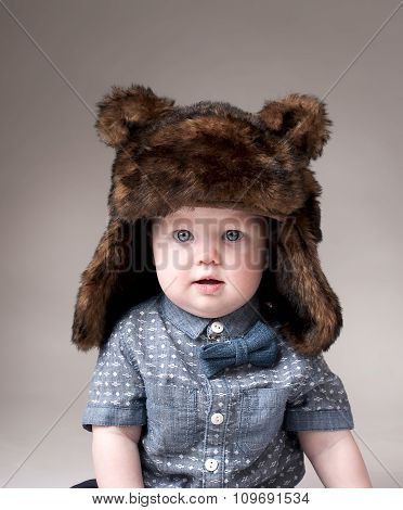 Funny baby boy in a winter fur hat cover gray background