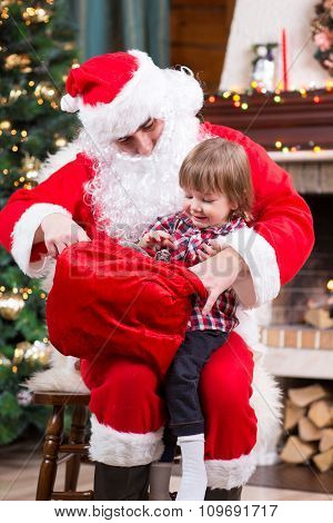 Santa Claus giving a present from sack to kid boy near the fireplace and Christmas tree at home