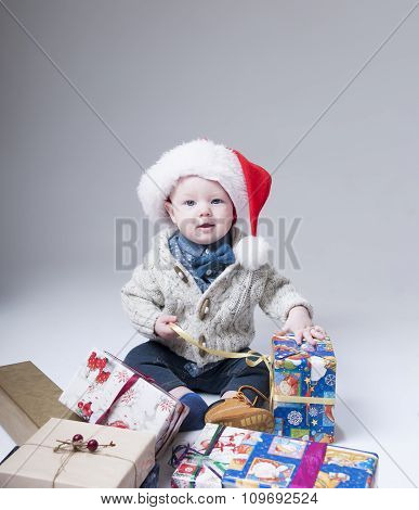 Cheerful  Baby  With Gift Boxes Wearing Santa Hat