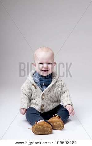 Smiling baby boy in knitted pullover