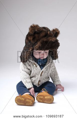 Funny Baby Boy In A Winter Fur Hat Cover Gray Background.
