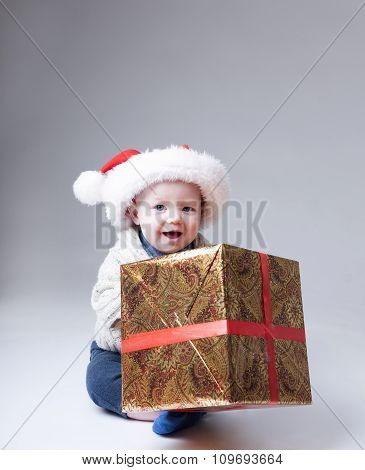 Funny Baby In Santa Hat Playing With A Big Gift Box.