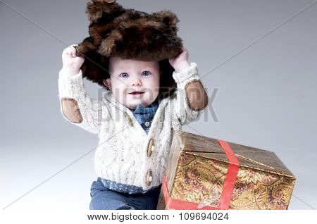 Funny Baby Boy In A Winter Fur Hat With Gift Box.