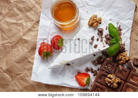 Breakfast Set With Chocolate, Brie, Strawberries And Honey On Craft Paper