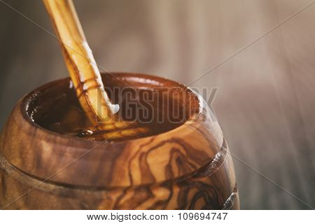 honey in olive wood pot with dipper on table