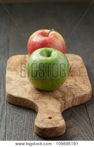 green and red apple on olive board