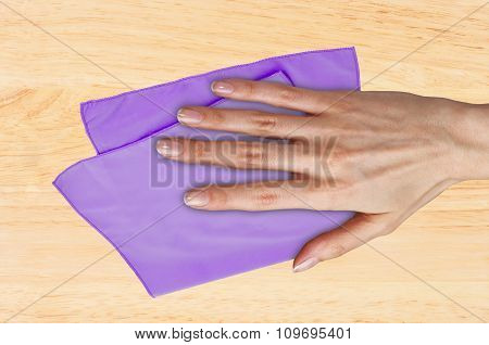 Hand Wiping Wooden Table With Violet Rag