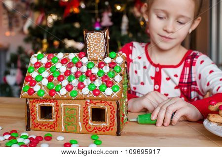 Little adorable girl decorating gingerbread house for Christmas