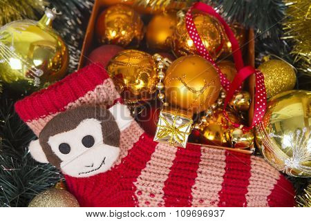Christmas Background With Colored Balls And Monkey On Red Sox.