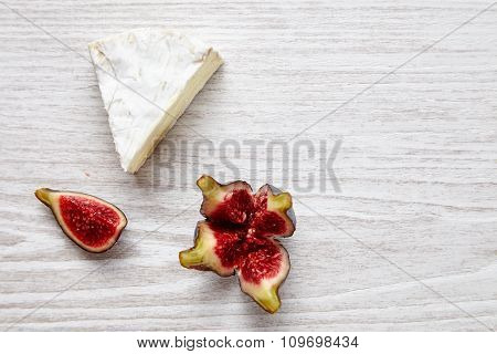 Piece Of Camember With Splittef Fig On White Wooden Table