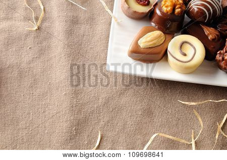 Assorted Bonbons In A White Dish With Straw Decoration Top
