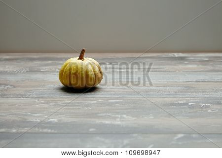 Pretty Small Mini Yellow Pumpkin On Grunge Wooden Table Alone