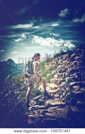 Vignette Retro Style Image of Young Woman Wearing Backpack Hiking on Rocky Mountainside Trail with View of Mountain Vista and Blue Sky with Clouds
