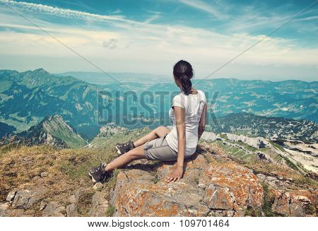 Panoramic Rear View of Woman Sitting on Rocky Ledge Enjoying the View of Extended Mountain Valley Landscape