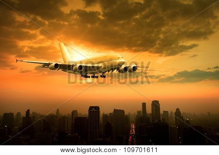 Passenger Jet Plane Flying Over Urban Scene Against Beautiful Sun Set Sky Use For Air Transport And