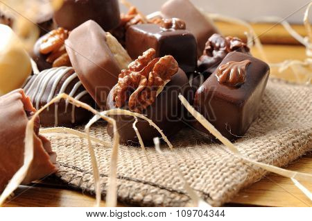 Close Up Bonbons Stacked On Burlap Sack On Wood Table
