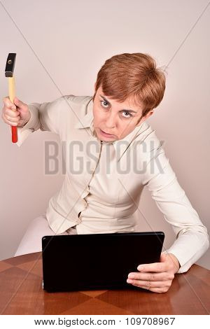 Angry businesswoman with a hammer and laptop