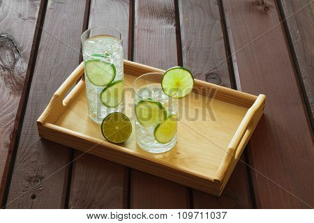 Two Drinks On Wooden Tray With Ice And Condensation On Glass