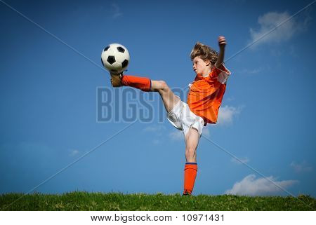 Child kicking playing football.